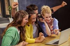 Amis de sourire à l'aide de l'ordinateur portable ensemble Photos stock