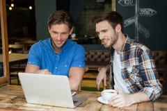 Amis de sourire à l'aide de l'ordinateur portable tout en se reposant à la table Photo stock