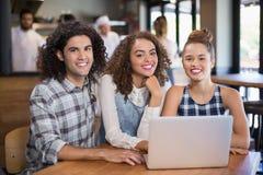 Amis de sourire à l'aide de l'ordinateur portable tout en se reposant dans le restaurant Photo libre de droits