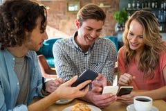 Amis de sourire à l'aide de leur téléphone portable Photos stock