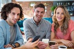 Amis de sourire à l'aide de leur téléphone portable Photographie stock
