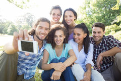 Amis de sourire à l'aide des dispositifs de media dans le parc Photos libres de droits
