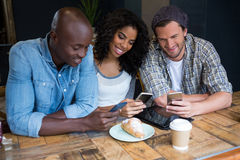 Amis de sourire à l'aide des téléphones intelligents à la table dans le café Image stock