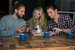 Amis de sourire à l'aide des téléphones intelligents à la table dans le cafétéria Image libre de droits