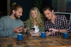 Amis de sourire à l'aide des téléphones intelligents à la table en café Photographie stock libre de droits