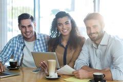 Amis de sourire à l'aide du comprimé numérique et de l'ordinateur portable dans le café Photos stock