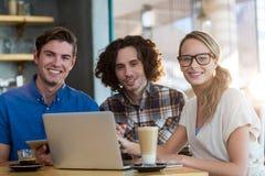 Amis de sourire à l'aide du comprimé numérique et de l'ordinateur portable dans le café Photographie stock