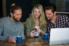 Amis de sourire à l'aide du téléphone intelligent à la table dans le cafétéria Photos libres de droits