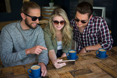 Amis de sourire à l'aide du téléphone intelligent à la table en café Photos stock