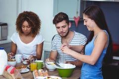 Amis de sourire à la table de petit déjeuner Image stock