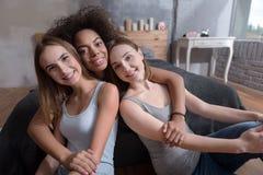 Amis de sourire étreignant dans la chambre à coucher à la maison Photos stock