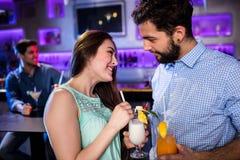 Amis de sourire agissant l'un sur l'autre les uns avec les autres au compteur de barre tout en ayant le cocktail Images stock