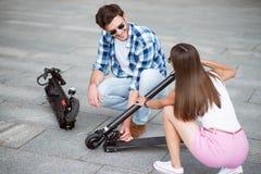 Amis de sourire agréables tenant le scooter de coup-de-pied Images stock