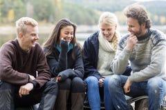 Amis de sourire appréciant camper sur au bord du lac Photos stock