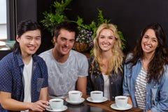 Amis de sourire appréciant le café ensemble Images stock