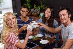 Amis de sourire appréciant le café ensemble Photo stock