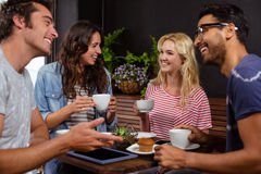 Amis de sourire appréciant le café ensemble Image stock