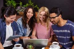 Amis de sourire appréciant le café ensemble et employer des technologies Images stock