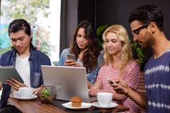 Amis de sourire appréciant le café ensemble et employer des technologies Photos libres de droits