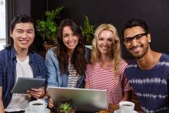 Amis de sourire appréciant le café ensemble et employer des technologies Image stock