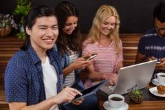 Amis de sourire appréciant le café ensemble et employer des technologies Photo stock