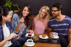 Amis de sourire appréciant le café ensemble et employer des technologies Photo libre de droits