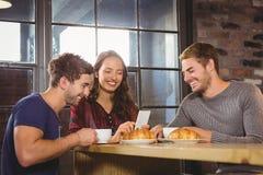 Amis de sourire appréciant le café et des croissants ensemble Photographie stock libre de droits