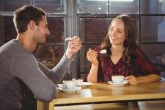 Amis de sourire appréciant le café et le gâteau ensemble Photos stock