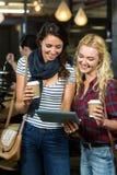 Amis de sourire appréciant le café tout en à l'aide du comprimé Photo stock