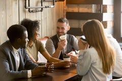 Amis de sourire appréciant le temps ayant ensemble le café en café Photographie stock libre de droits