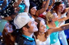 Amis de sourire au concert dans le club Photographie stock libre de droits