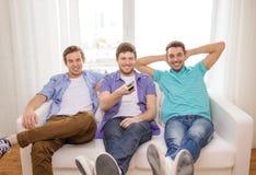 Amis de sourire avec à télécommande à la maison Photographie stock libre de droits
