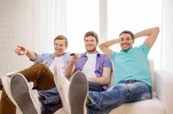 Amis de sourire avec à télécommande à la maison Photos libres de droits