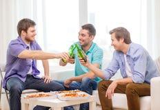 Amis de sourire avec de la bière et la pizza traînant Photographie stock
