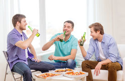 Amis de sourire avec de la bière et la pizza traînant Photos stock