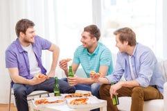 Amis de sourire avec de la bière et la pizza traînant Images stock