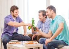 Amis de sourire avec de la bière et la pizza traînant Image stock