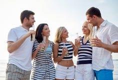 Amis de sourire avec des boissons dans des bouteilles sur la plage Photos libres de droits