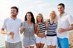 Amis de sourire avec des boissons dans des bouteilles sur la plage Image stock