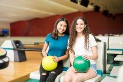 Amis de sourire avec des boules de bowling dans le club Photographie stock