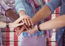 Amis de sourire avec des mains ensemble contre le drapeau américain Images stock