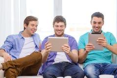 Amis de sourire avec des ordinateurs de PC de comprimé à la maison Photographie stock libre de droits