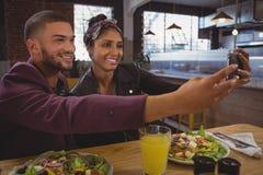 Amis de sourire avec des saladiers prenant le selfie en café Photo stock