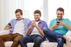 Amis de sourire avec des smartphones à la maison Photographie stock