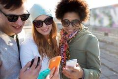 Amis de sourire avec des smartphones Images stock