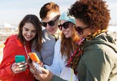 Amis de sourire avec des smartphones Photo libre de droits