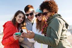 Amis de sourire avec des smartphones Photos libres de droits