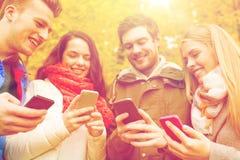 Amis de sourire avec des smartphones en parc d'automne Images libres de droits