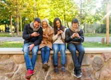 Amis de sourire avec des smartphones en parc de ville Images stock