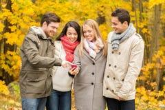 Amis de sourire avec des smartphones en parc de ville Photos libres de droits